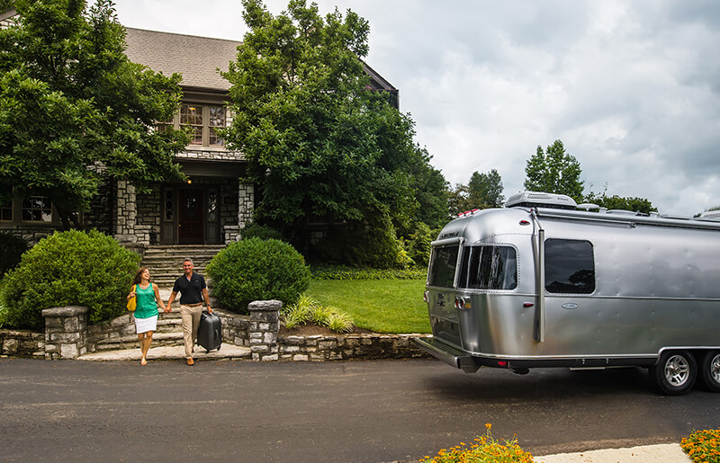 Airstream RV Classic Travel Trailer in front of house