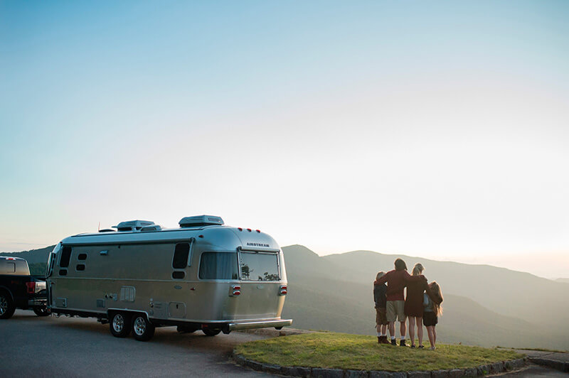 Family with Airstream RV Flying Cloud Travel Trailer by mountains