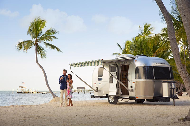 Couple on beach with Airstream Tommy Bahama Travel Trailer