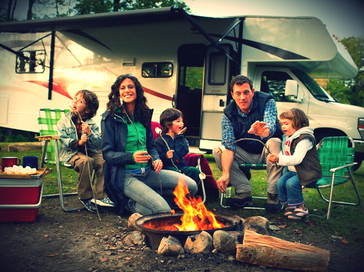 Family sitting by campfire in front of RV