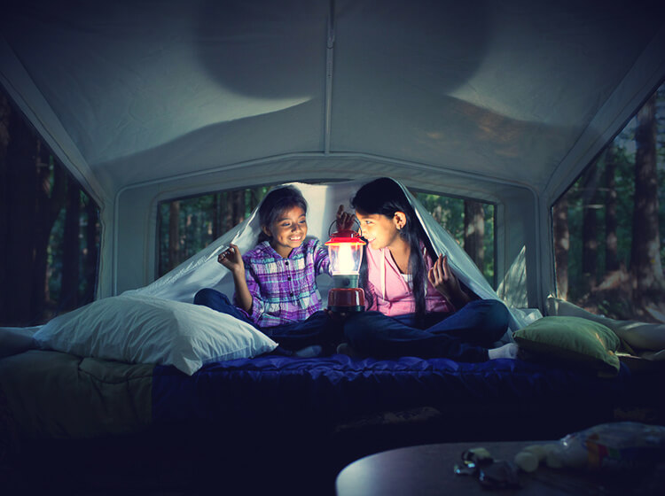 Girls inside RV holding lantern at night