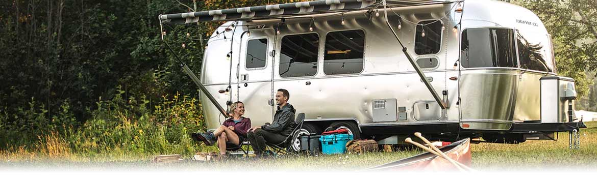Couple sitting by their Airstream RV