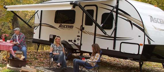 People lounging outside of an Ascend travel trailer with the canopy up surrounded by trees.