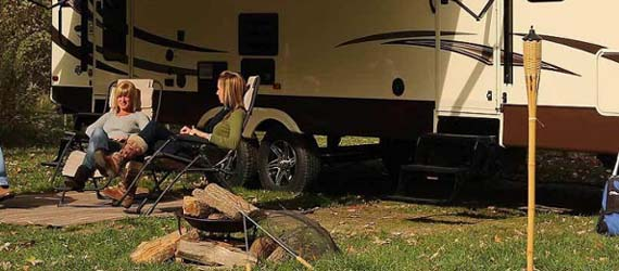 ladies sitting in front of Travel Trailer