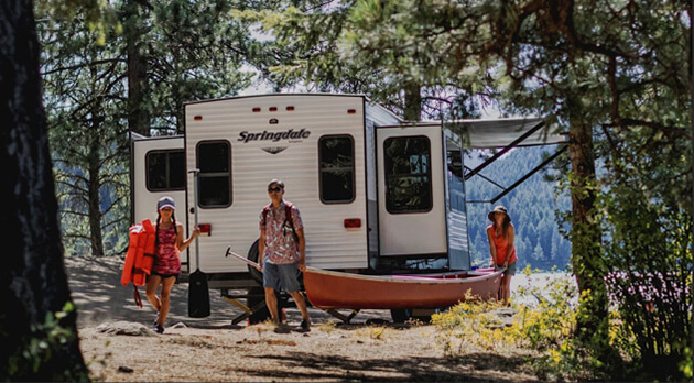 Family camping in front of Travel Trailer