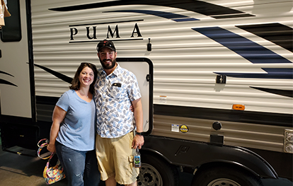 This couple is ready to go camping in their new Puma Travel Trailer