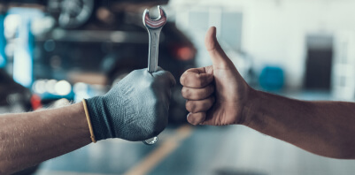 One hand holding a wrench and another giving a thumbs-up.