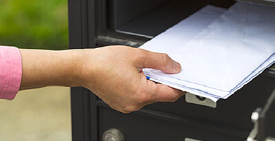 Someone placing mail into a mailbox.