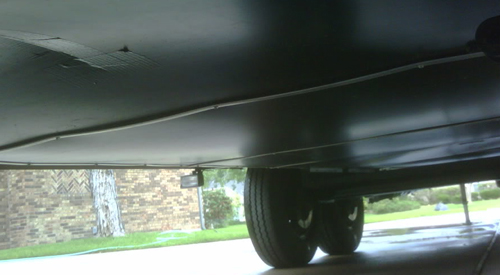how to winterize your rv and get it ready for storage, picture of the underneath black plastic wrapping of a travel trailer, plastic floor wrapping underneath a rv