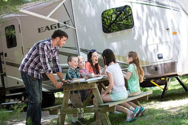 Family sitting at a picnic table outside their RV.