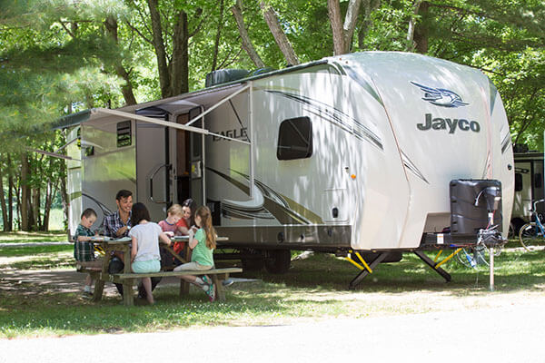 Family sitting at a picnic table outside their RV. Full view of RV.