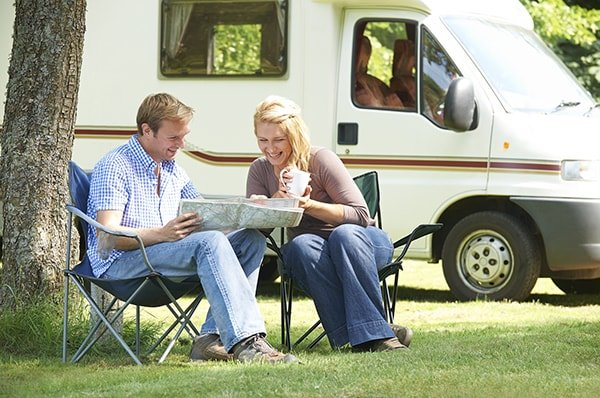 Couple reading next to their Motor Home