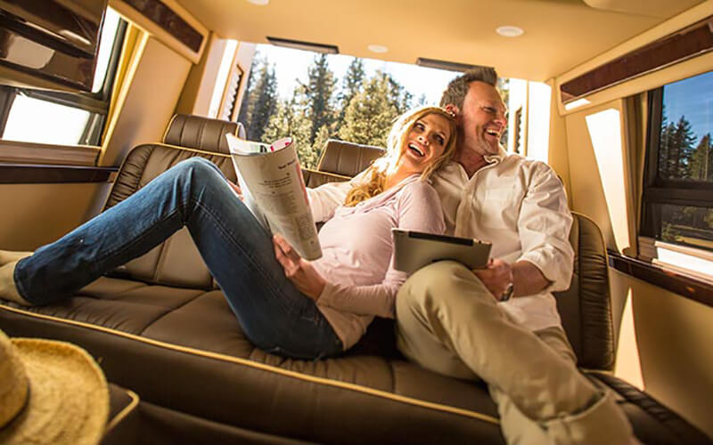 Couple Sitting Inside Midwest Automotive Designs Daycruiser Motor Home